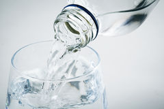 Pouring water on a glass on white background Royalty Free Stock Photo