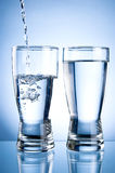 Pouring water into glasson and Glass of water Royalty Free Stock Photos