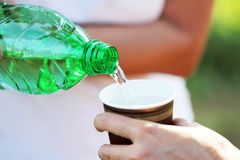 Pouring water from green bottle. Pouring water from green plastic bottle royalty free stock photo