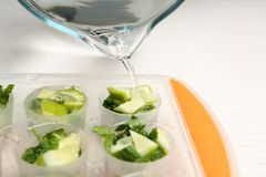 Pouring water into ice cube with lime slices and mint on table, closeup. Pouring water into ice cube tray with lime slices and mint on table, closeup stock photos