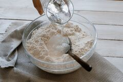 Free Pouring Water Over Flour In A Bowl For Making Bread Stock Image - 181306411