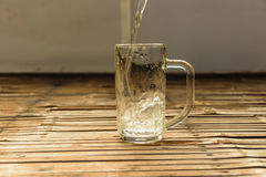 Pour a glass of water on a wooden table. Pouring water, put a transparent glass placed on the table the old bamboo. Finality is a refreshing drink, has wanted to Stock Images