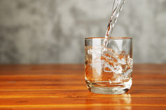 Pouring water splash into a glass. Royalty Free Stock Image