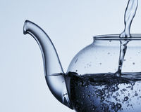 Pouring water into a teapot Stock Photography