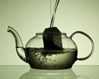 Pouring water into teapot with teabag Royalty Free Stock Photography