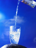 Pouring water to a glass Stock Images