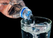 Pouring water to a glass isolated on black background royalty free stock image