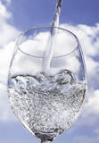 Pouring water into a wine glass. Water being poured with the sky in the background Royalty Free Stock Photography