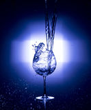Pouring water into wine glass with black background blue white balance Royalty Free Stock Images