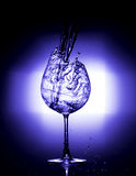 Pouring water into wine glass with black background blue white balance Stock Photo