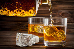 Pouring Whiskey From Bottle In The Glasses Stock Photography