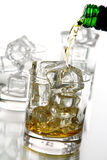 Pouring whiskey into the glass. Pouring cold whiskey into the glass isolated over white background Royalty Free Stock Images