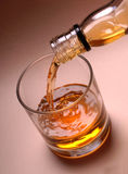 Pouring Whiskey into Glass. Whiskey or Bourbon being poured from a bottle into a tumbler or low ball glass Stock Images