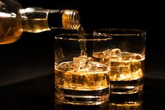 Pouring whiskey into a glass from bottle with ice cubes on black. Background stock images