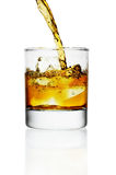 Pouring whiskey in glass with ice Stock Images