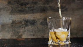 Pouring whiskey in glass with ice stock footage
