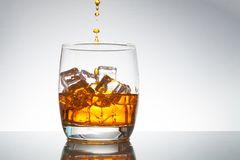 Pouring whiskey in glass. With ice royalty free stock photo