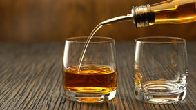 Pouring whiskey into the glass on a wooden table. Pouring a scotch whiskey into glass on a wooden table Stock Image