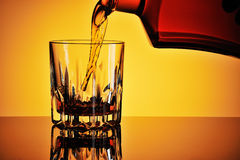 Pouring whisky into a glass Stock Photo