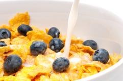 Pouring white milk into a bowl of breakfast flakes Stock Photo