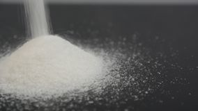 Pouring white sugar over black surface. In studio shot, neutral background stock video footage