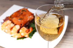 Pouring white wine and background. Pouring white wine and seafood background Stock Image