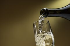 Pouring white wine into a wineglass Royalty Free Stock Image