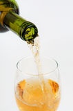 Pouring white wine from bottle into the wineglass Stock Photos