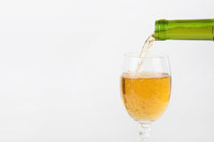 Pouring white wine from bottle into the wineglass Stock Photography