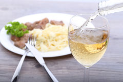 Pouring white wine and food Stock Images