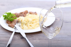 Pouring white wine and food background. Pouring white wine and plate with spagetti Royalty Free Stock Photography