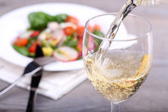 Pouring white wine into glass. And food background royalty free stock images