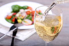 Pouring white wine into glass. And food background Royalty Free Stock Photography