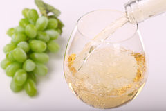 Pouring white wine. Into a glass and grape on the table Royalty Free Stock Photography