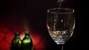 Pouring white wine into glass shooting, two bottles and red background, alcohol drink filling goblet.  stock footage