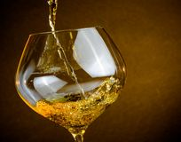 Pouring white wine into a glass with space for text, warm atmosphere. Pouring white wine into a glass on golden background with space for text, warm atmosphere Stock Image