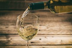 Pouring white wine in a glass on wooden background royalty free stock image