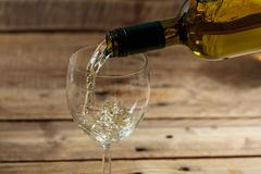 Pouring white wine in a glass on wooden background Stock Photos
