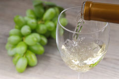 Pouring white wine and grape Stock Photos