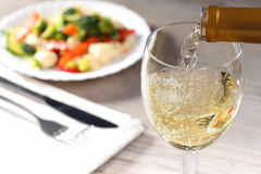 Pouring white wine and salad Royalty Free Stock Image