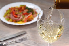 Pouring white wine and salad Stock Photo