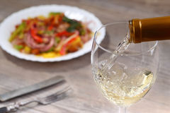 Pouring white wine and salad Stock Photos