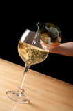 Pouring white wine into a wineglass Stock Images