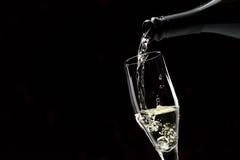 Pouring white wine into a wineglass Stock Photos