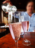 Pouring Wine. Pouring pink champagne or sparkling wine out of a bottle into a glass royalty free stock image