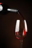 Pouring wine. Pouring red wine in a glass. Close up Stock Image