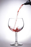 Pouring wine. Pouring red wine in the glass white background Stock Photo