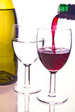 Pouring wine. Red wine being poured against a white background stock image