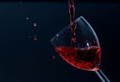 Pouring wine. Wine being poured into a wine glass on an angle Stock Image