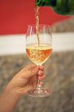 Pouring wine from a bottle into a wineglass. Stock Photo